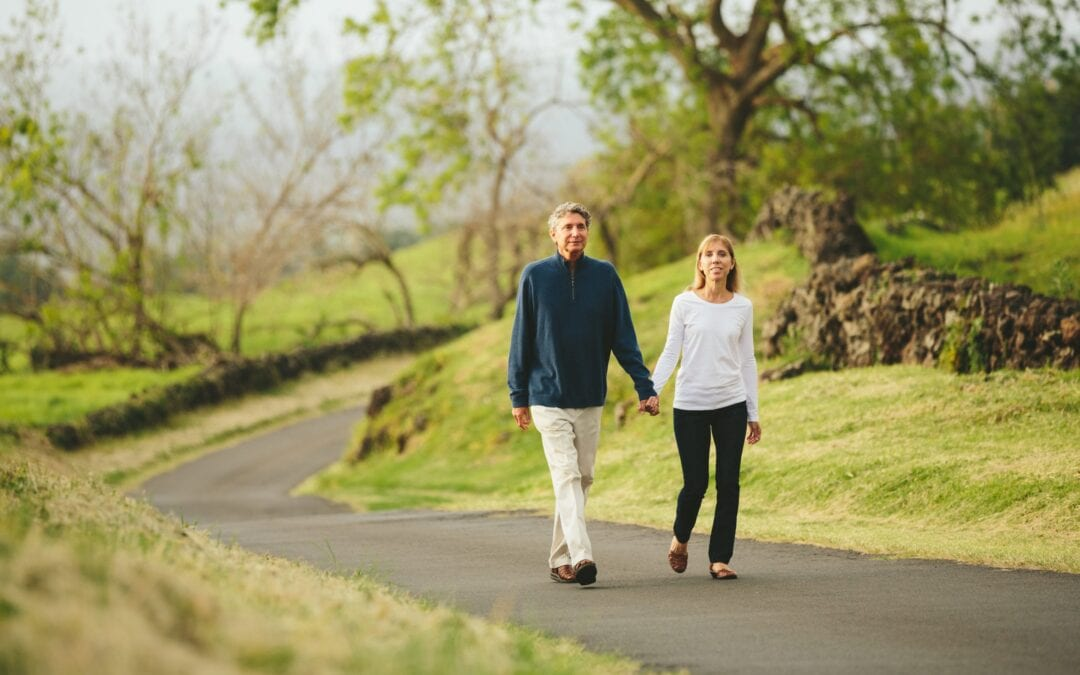 Middle aged couple walking hand in hand along wooded area