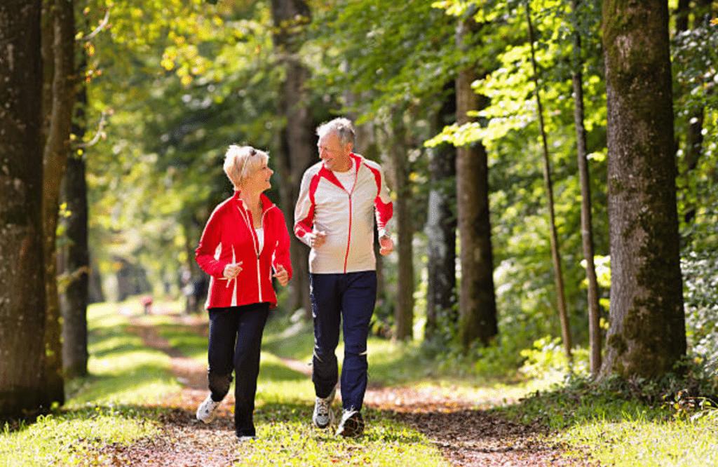 senior couple jogging through wooded area