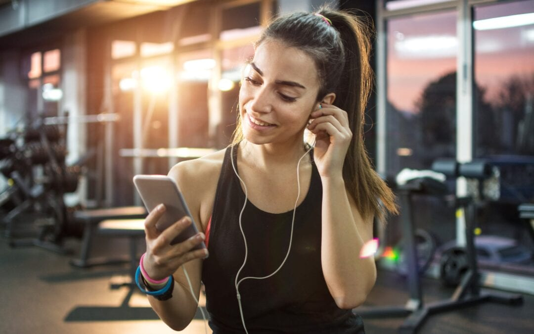 Young lady at the gym with ear phones in looking at her phone
