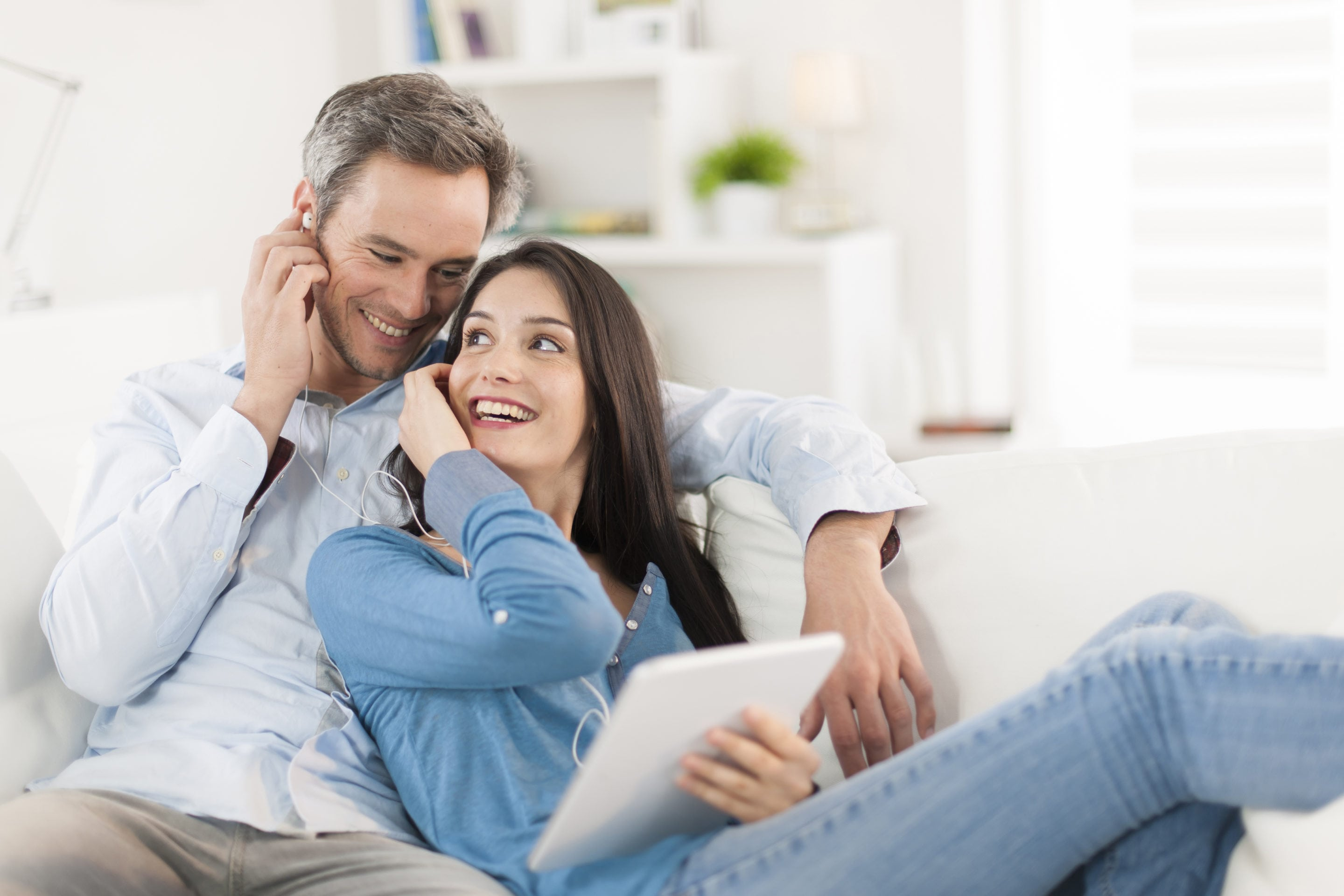 cheerful couple sharing music on digital tablet in sofa at home | Beltone Hearing