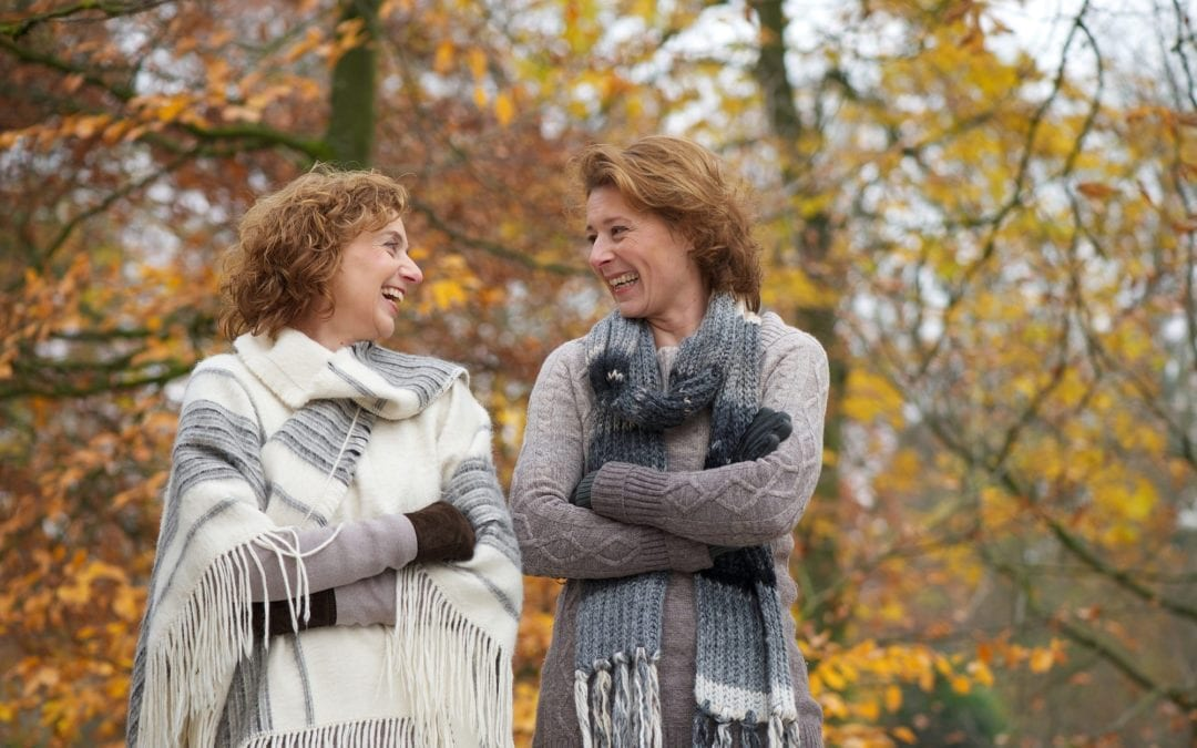Mature friends smiling at eachother in a park in autumn