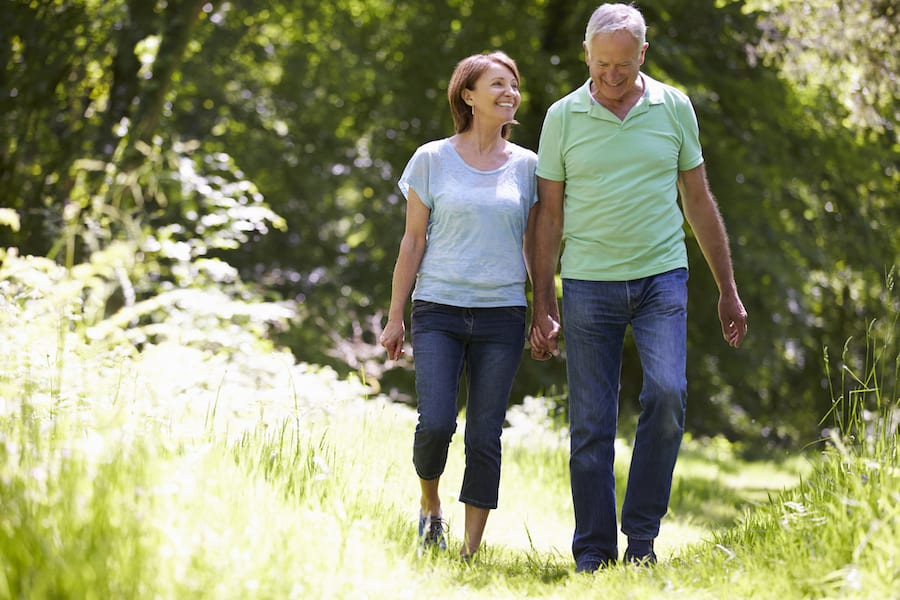 Middle-aged couple walking outdoors holding hands | Beltone Hearing