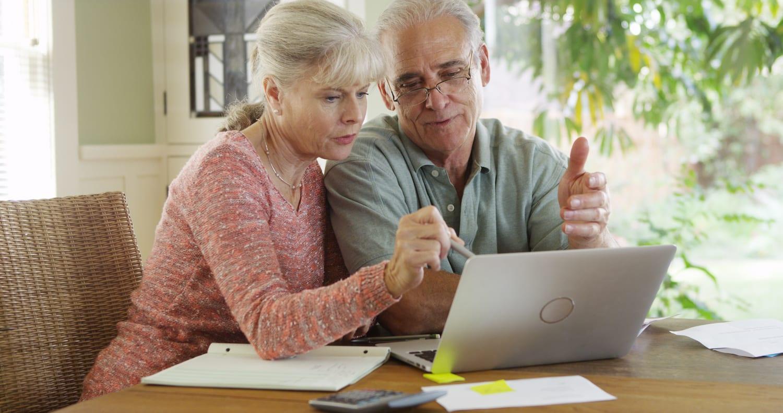 Senior couple using laptop computer to pay bills   Beltone Hearing