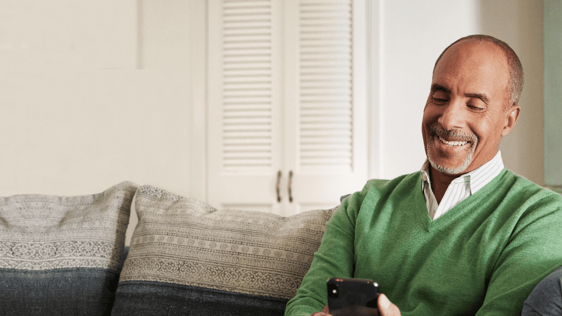 Middle aged man sitting on the sofa smiling at his phone